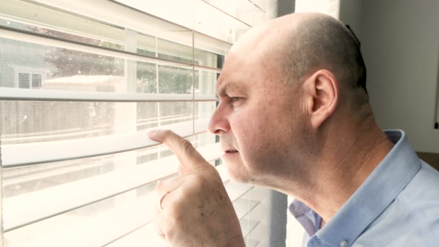 serious mature man looking through his home window - paranoia stock videos & royalty-free footage