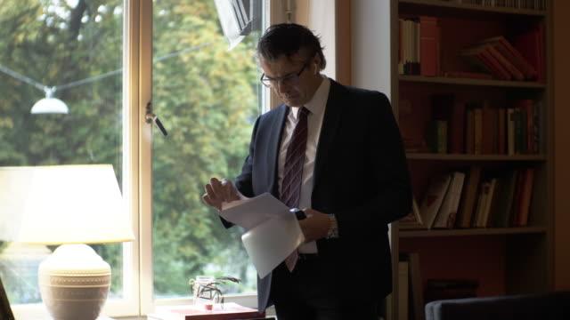 vidéos et rushes de serious mature man wearing eyeglasses while reviewing documents in law firm - avocat juriste
