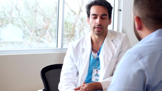 serious mid adult male doctor discusses diagnosis with male patient - lab coat stock videos & royalty-free footage