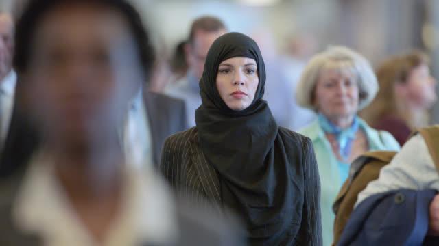 vídeos y material grabado en eventos de stock de slo mo. serious middle eastern businesswoman walks through crowded terminal in airport. - inmigrante