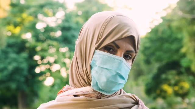 serious middle eastern muslim woman looking at the camera wearing a protective face mask - headscarf stock videos & royalty-free footage