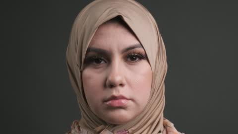 vídeos y material grabado en eventos de stock de seria joven musulmana de oriente medio mirando a la cámara - sin expresión