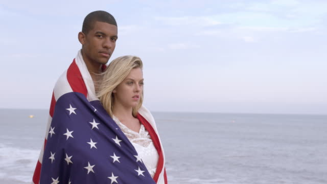 serious mixed race couple wrapped in us flag at beach 4k - vesper stock stock videos & royalty-free footage
