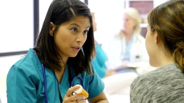 serious nurse talks with patient about a diagnosis - nurse stock videos & royalty-free footage