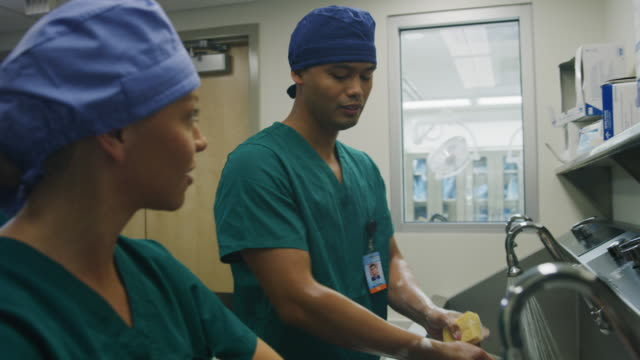 serious nurses talking while scrubbing for surgery then smiling when doctor arrives / salt lake city, utah, united states - hygiene stock-videos und b-roll-filmmaterial
