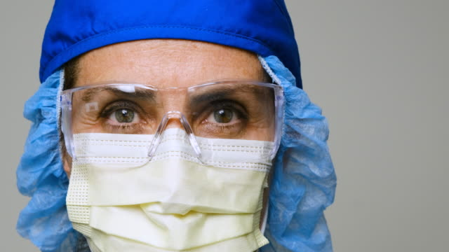 serious, overworked, female health care worker - protective workwear stock videos & royalty-free footage