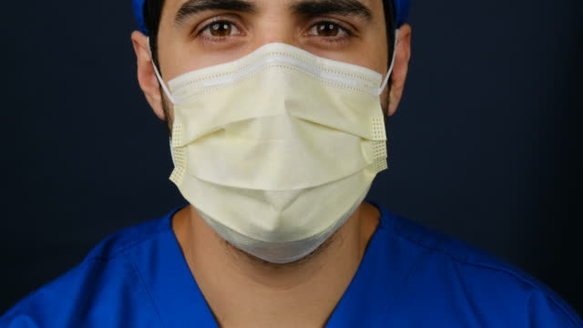 vídeos de stock e filmes b-roll de serious overworked healthcare worker looking at the camera using a surgical mask - enfermeiro