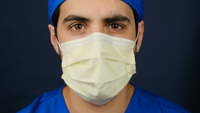 serious overworked healthcare worker looking at the camera using a surgical mask - laboratory coat stock videos & royalty-free footage