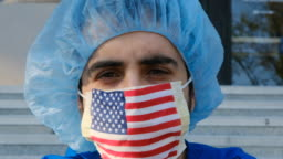 serious overworked, male young health care worker a US flag protective mask looking at the camera