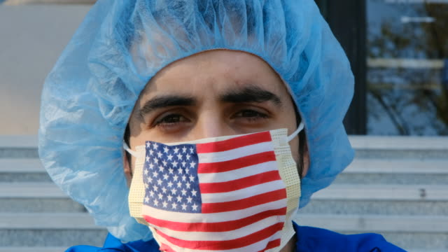 serious overworked, male young health care worker a us flag protective mask looking at the camera - heroes stock videos & royalty-free footage