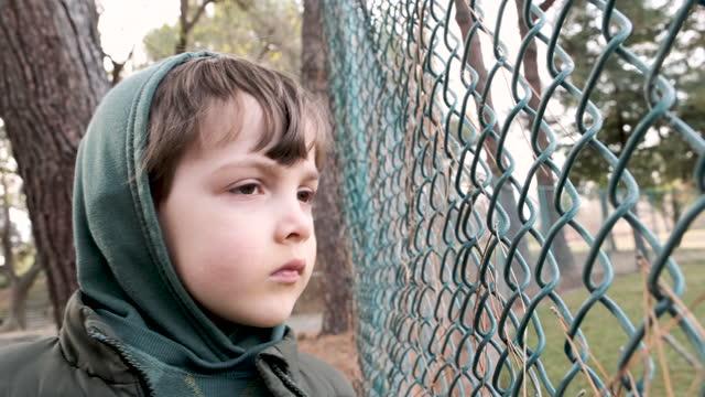 stockvideo's en b-roll-footage met ernstig peinzend kind dat door een omheining kijkt - negative emotion