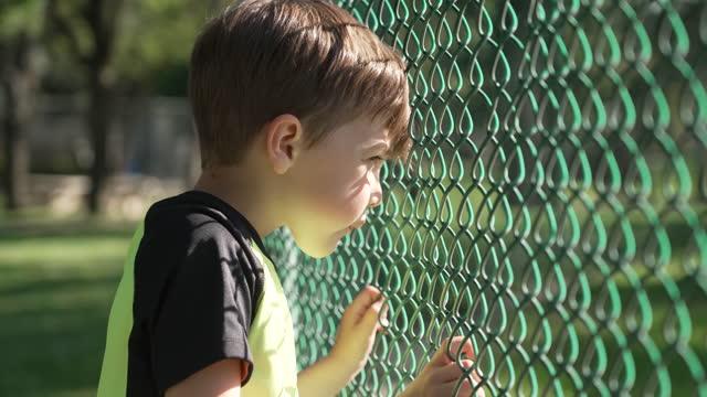 フェンスを見て深刻なペンシブ小さな男の子 - 自閉症点の映像素材/bロール