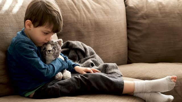 vídeos y material grabado en eventos de stock de niño pensativo serio acariciando a su gato de juguete de peltió - un solo niño