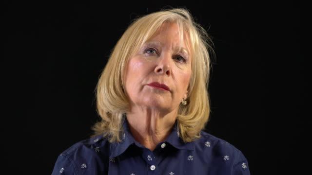 stockvideo's en b-roll-footage met ernstige gepensioneerde vrouw tegen zwarte achtergrond - formeel portret