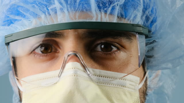 serious sad overworked healthcare worker looking at the camera using a surgical mask - protection stock videos & royalty-free footage