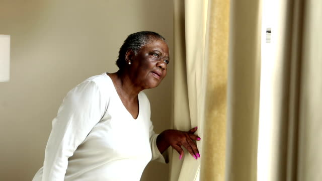 Serious senior African-American woman looks out window