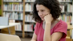 Serious student sitting at table in library and working with laptop