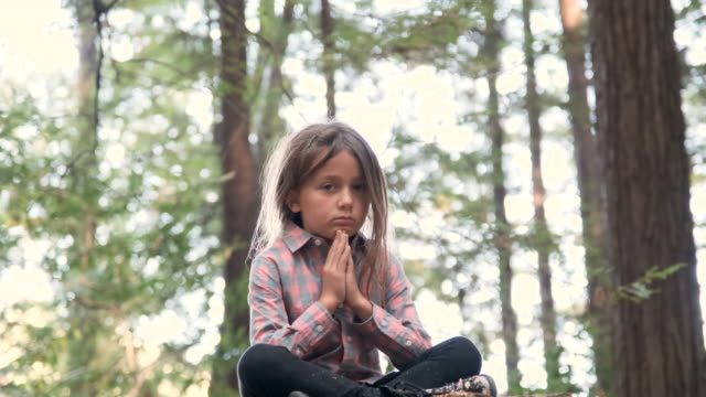 serious thinking little girl sitting in the woods - girl sitting cross legged stock videos & royalty-free footage