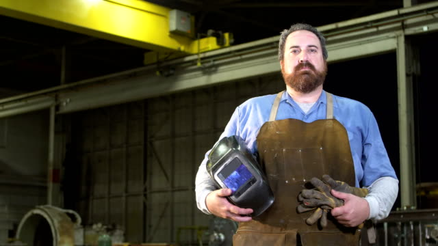 serious welder holding his gloves and mask - glove video stock e b–roll