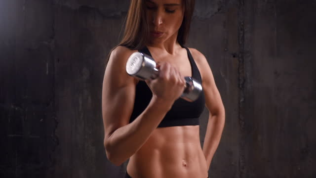 Serious woman doing biceps exercise with right breathing