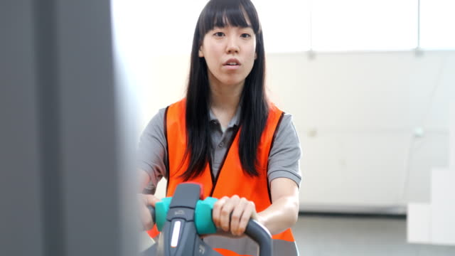 Serious woman using equipment in industry