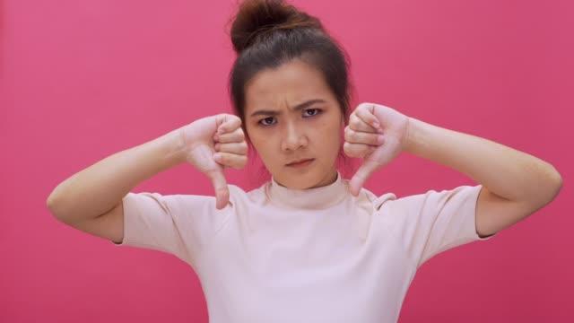 ernst frau finger sehe kein handzeichen in die kamera winken isoliert rosa hintergrund 4 k - chinesischer abstammung stock-videos und b-roll-filmmaterial