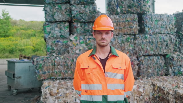 serious workman standing outdoors in recycling facility - nachhaltigkeit stock-videos und b-roll-filmmaterial