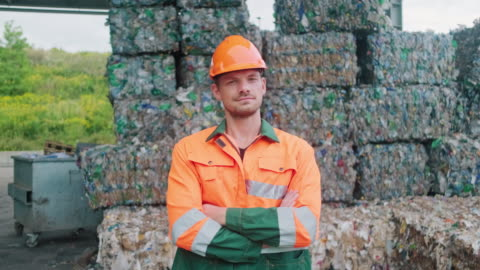 stockvideo's en b-roll-footage met serious workman standing outdoors bij recycling facility - recycling