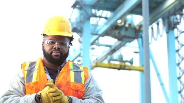 Serious young African-American man working at seaport