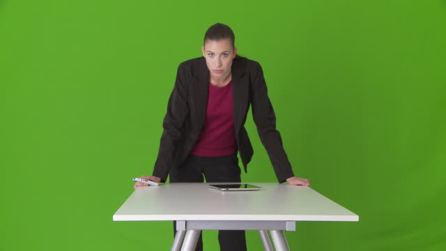 serious young businesswoman executive leaning on desk - tre quarti video stock e b–roll