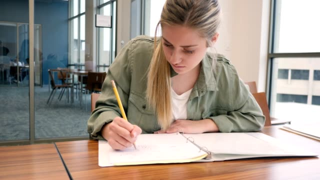 serious young college student doodles in notebook before class - back to school stock videos & royalty-free footage