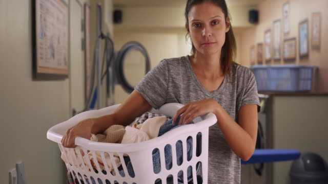 serious young woman holding basket of dirty clothes in laundry room - imperfection stock videos & royalty-free footage