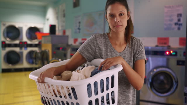 serious young woman in laundry room with machines holding basket of clothes - tvättmedel bildbanksvideor och videomaterial från bakom kulisserna
