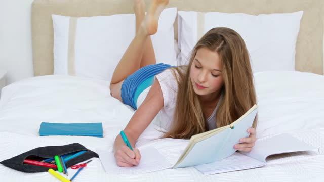 vídeos de stock, filmes e b-roll de serious young woman studying while lying - reclinando