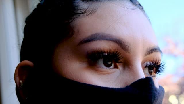 窓から見て保護フェイスマスクを身に着けている深刻な若い女性 - プエルトリコ人点の映像素材/bロール