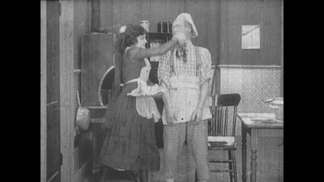 1917 a servant pushes a cook into a dough filled pan - collaboratore domestico video stock e b–roll