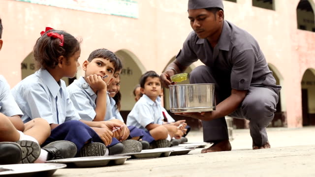 servant serving midday meal to school students, haryana, india - school building stock videos & royalty-free footage