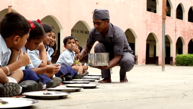 servant serving midday meal to school students, haryana, india - schoolgirl stock videos & royalty-free footage