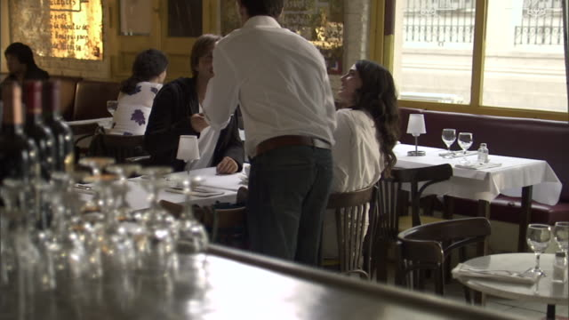 selective focus ms server picking coffees up from bar/ r/f server taking coffees to man and woman sitting at cafe table/ buenos aires, argentina - unrecognisable person stock videos & royalty-free footage