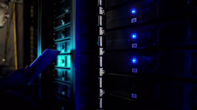 server-raum-techniker arbeiten mit tablet im server-bereich - klemmbrett stock-videos und b-roll-filmmaterial
