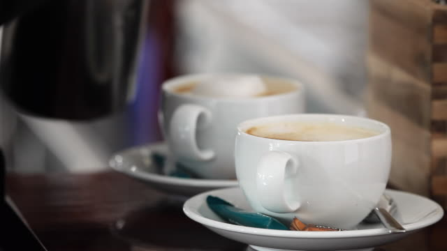 cu server serving foam on two coffee drinks / palma de mallorca, mallorca, baleares, spain - coffee cup stock videos & royalty-free footage