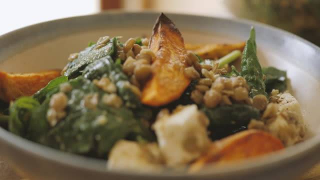 service green lentil, spinach, and feta cheese salad with roasted sweet potato wedges - spinach salad stock videos & royalty-free footage