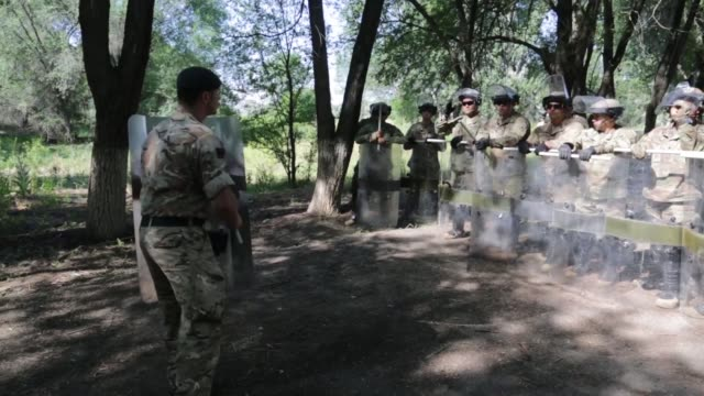Service members from Kazakhstan United Kingdom United States of America Tajikistan and Kyrgyzstan train together with riot shields in simulated crowd...