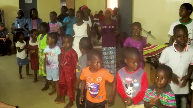 service members from nigerien air base 101 in niamey spend some time with the children of a nearby orphanage. - ニアメ点の映像素材/bロール