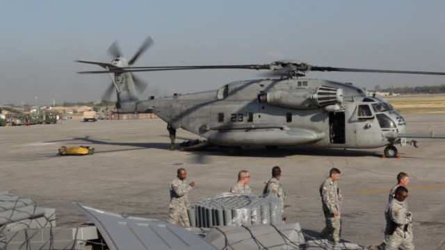 u.s. service personnel move past an american helicopter at a haitian airfield. - haiti stock-videos und b-roll-filmmaterial