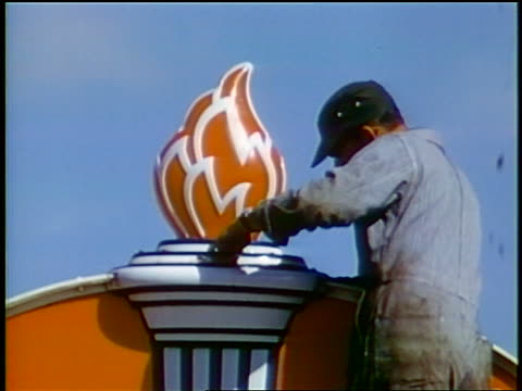 1958 service station attendant attaching flame to top of service station sign / newsreel - filling station attendant stock videos and b-roll footage