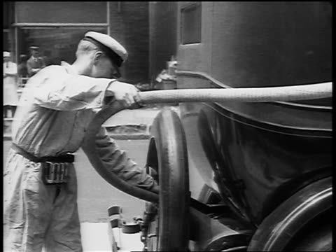 b/w 1929 service station attendant pumping gas into car at gas station / newsreel - gas station attendant stock videos and b-roll footage