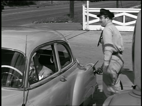 b/w 1951 service station attendant pumping gas + talking to man in car / industrial - gas station attendant stock videos and b-roll footage