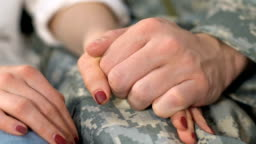 Serviceman and girlfriend holding hands closeup, spouse support, homecoming