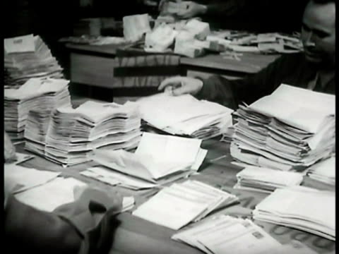 Serviceman emptying bag of bound Vmail soldiers opening Vmail sheets into stacks for microfilming CU Vmail letter covers CU Letter 'Dear Son Mother...
